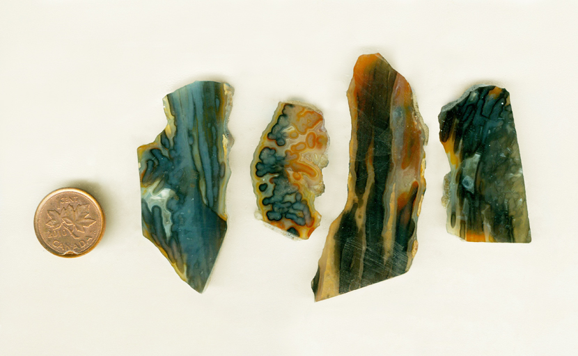Four slabs of stalactite agate, orange blue and yellow patterns.