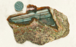 White lines in star-shaped agate, enclosed in green, orange and purple rhyolite.