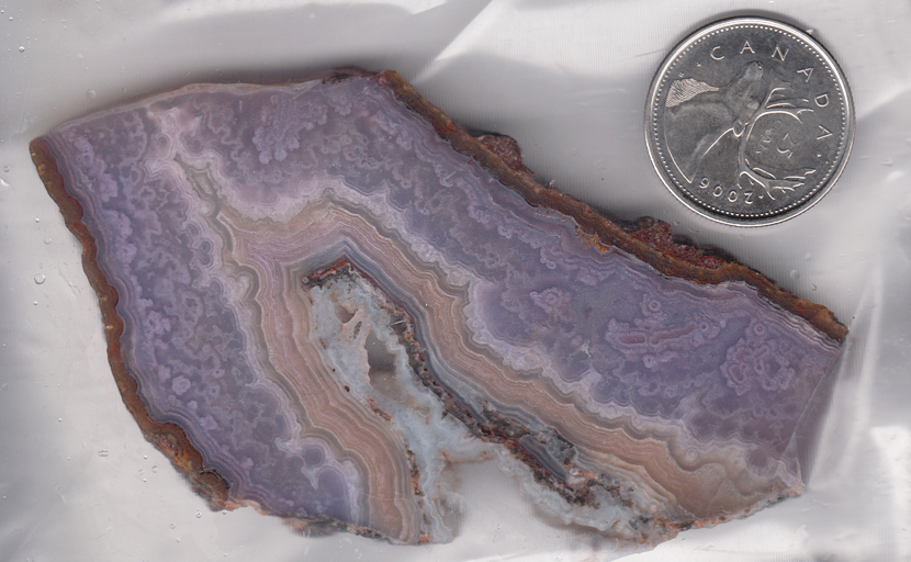 Slab of Mexican Royal Aztec Agate, with purple lace patterns and a band of pink.