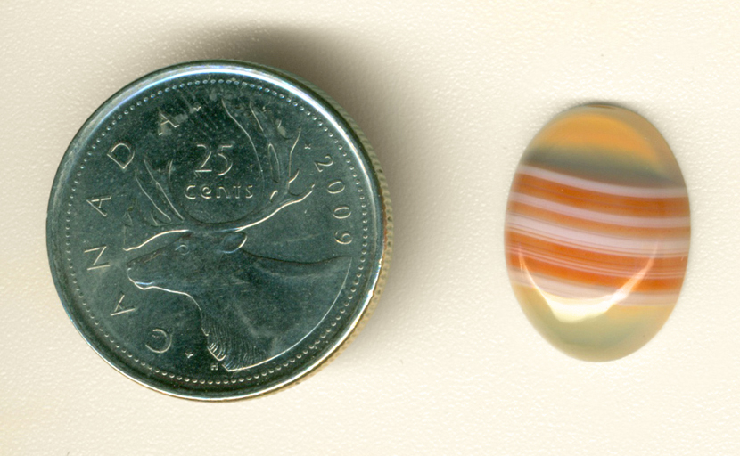 Orange and white striped cabochon of translucent agate from Uruguay.