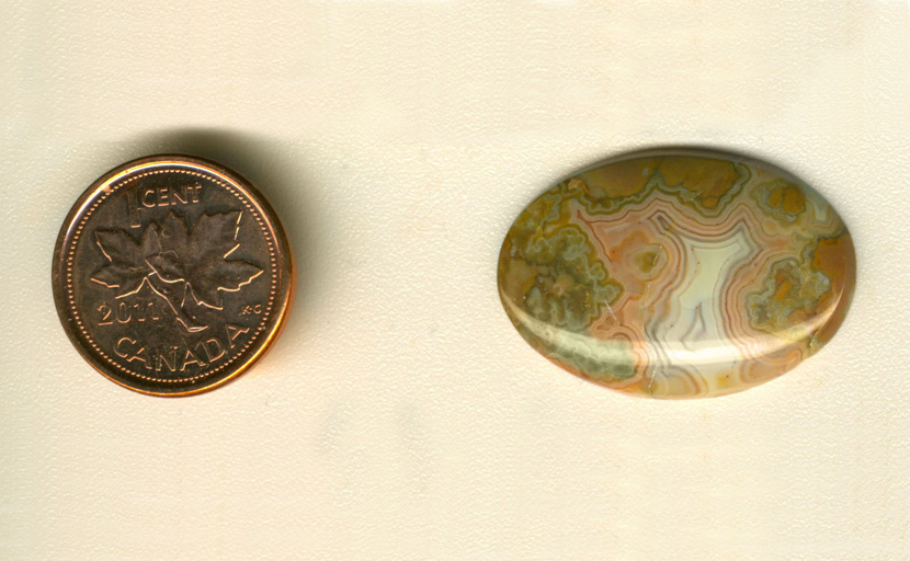 Calibrated oval polished Fairburn Agate cabochon from Nebraska or South Dakota, with orange, mint-green and blue patterning around a white fortification, on an orange background.