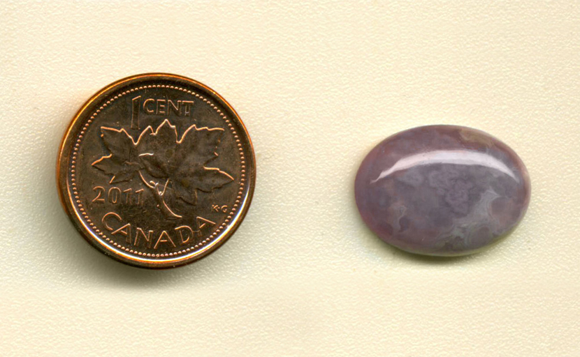 Calibrated polished oval Royal Aztec Agate cabochon from Mexico, deep purple with lace and plume patterns.