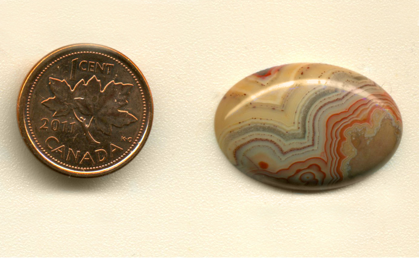 Calibrated oval polished Fairburn Agate cabochon from Nebraska or South Dakota, with successive layers of orange, blue, purple and yellow.