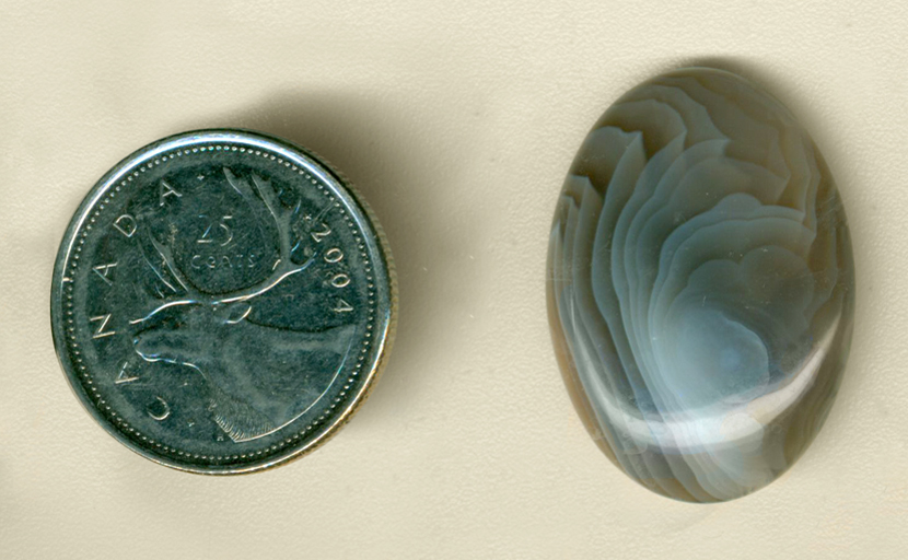 Calibrated oval polished Botswana Agate cabochon, with swirls of blue and gray folded over on themselves.