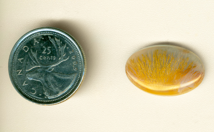 Calibrated polished Nipomo Sagenite cabochon, with a fan shape of golden-orange needles in bluish chalcedony.