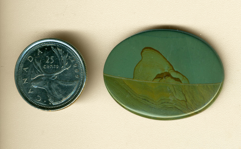 Cabochon of Succor Creek Jasper from Washington, with a greenish-blue sky and a desert below it, patterned and with a central mountain.