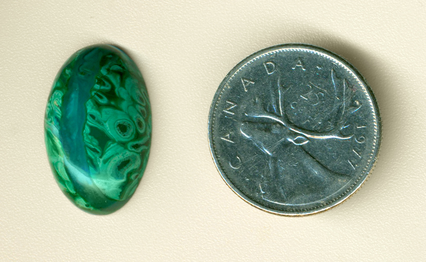Bright green tubes and a blue line in a cabochon of Malachite in Gem Silica from the Inspiration Mine, Globe County, Arizona.