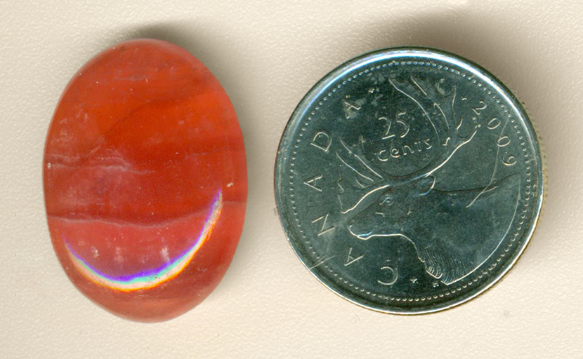 Bright pink banded cabochon of Rhodochrosite from Argentina.