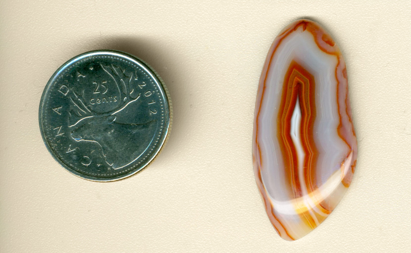 Freeform polished Malawi Agate cabochon, with orange and red layers around and inside a bluish-gray body.