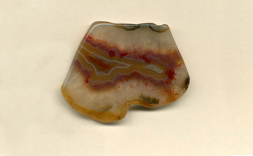 A freeform Coyamito Agate from Mexico, with a central band of yellow fortifications, which, in turn, is covered with flame red and purple flame patterns.