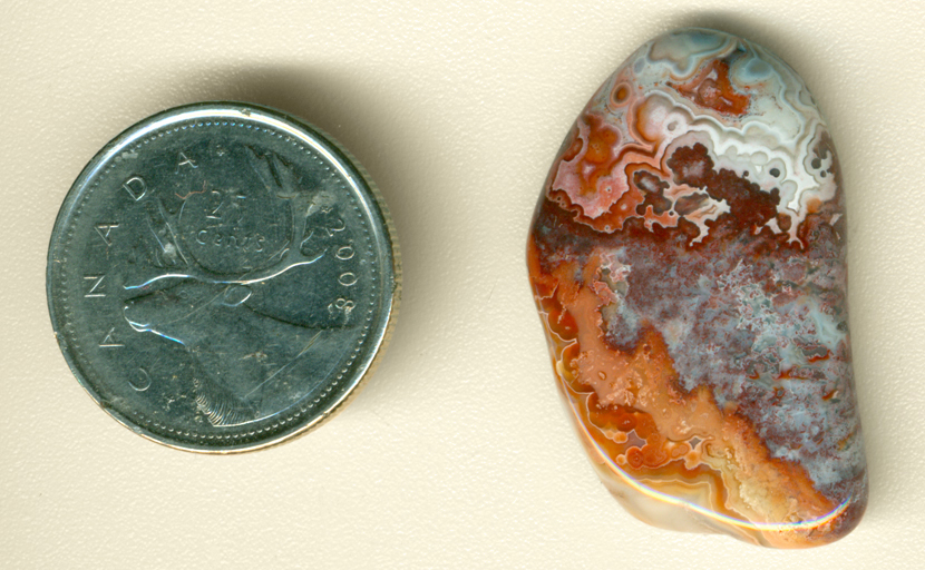 White fortifications and orange lace on either side of a blue and red space, arranged like a miniature map, in a polished freeform Crazy Lace Agate from Mexico.