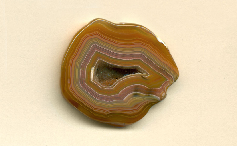 A polished freeform Coyamito Agate from Mexico, with a fortification pattern that includes layers of purple, green, yellow, orange and red, with a druzy crystal vug in the center.