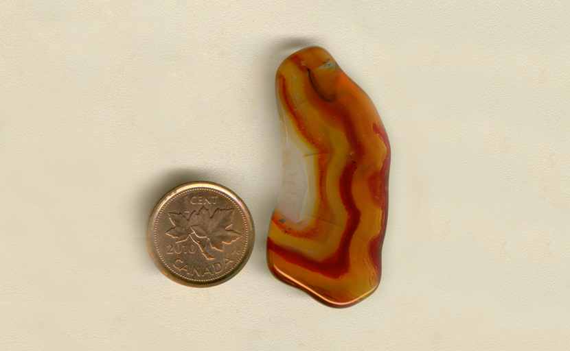 Freeform polished Laguna Agate from Mexico, with a half pattern of orange, yellow and russet brown rippling colors.