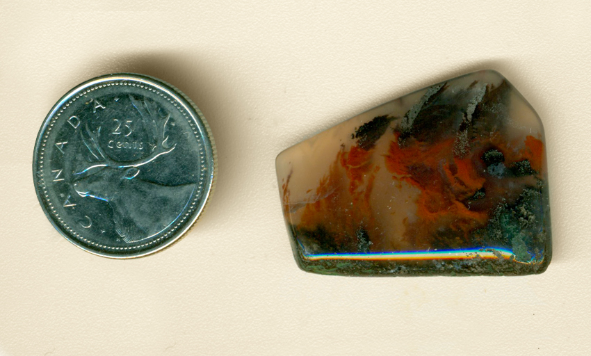 Freeform polished Mexican Flame Agate cabochon, with a black and green ground, red flames, and black smoke up above, all trapped in clear agate.