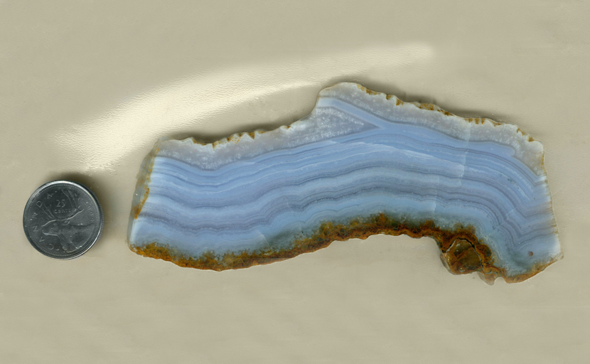 A slab of Blue Lace Agate from Namibia, with bright blue stripes in borders of reddish brown.