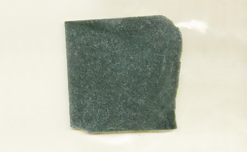 A square slab of Nephrite Jade from Wyoming, dark green mottled with lighter color.