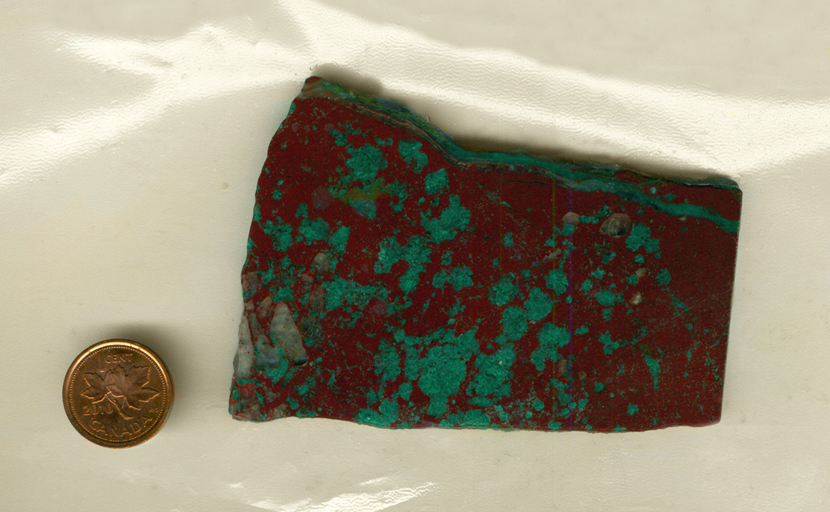 A slab of Cuprite and Malachite from Arizona, with bright green spots on a reddish brown surface, and one stripe of green stretching across the top.