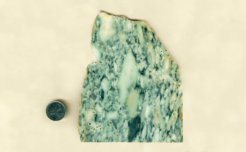 A slab of Vert Antique Marble, with blue-green running markings and brown dots.