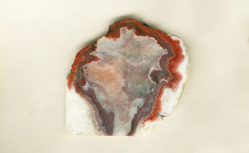 Prairie Agate slab with red bands and purple inside them.