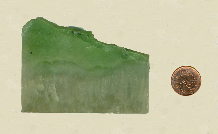 A bright green slab of Jade from Siberia, with lighter grass patterns along the bottom.