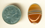 Orange and coffee colors separated by horizontal white lines in a cabochon of Uruguay Agate.