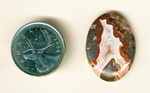 "Polished Crazy Lace Agate cabochon, with an ""A""-shaped pink fortification and red and metallic moss inclusions."