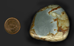 A freeform polished cabochon of Owyhee Picture Jasper from Idaho or Oregon, with a slate blue sky and brown and yellow ground on three sides.