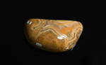 A freeform cabochon of Fairburn Agate from Nebraska or South Dakota, orange and brown in a fortification pattern, lacy around the edges.