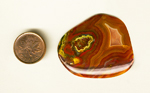 Freeform polished Laguna Agate cabochon from Mexico, with a bright yellow and red pattern on the right, and muted reds, browns, and pinks on the rest of the surface.
