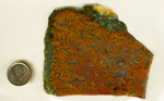 A slab of jasper packed with red and orange coral patterns, surrounded on two edges with green and yellow.