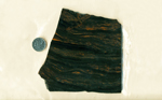 Slab of black obsidian with dark brown swirls against the translucent background.