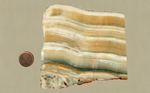 Onyx slab with honey-colored and white stripes, arranged on top of a darker stripe and reddish patterns underneath it.