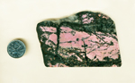 A slab of Rhodonite from Rosemund, California, with a strong pink background and glittering black lines and patches in the foreground.